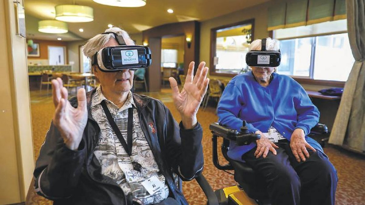 Two older adults testing out new technology by Age-tech